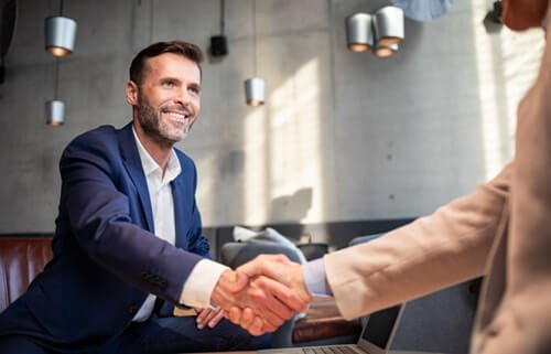 Trusted employee and employer shaking hands